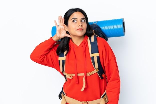 Junges bergsteigermädchen mit einem großen rucksack auf weißer wand, die etwas hört