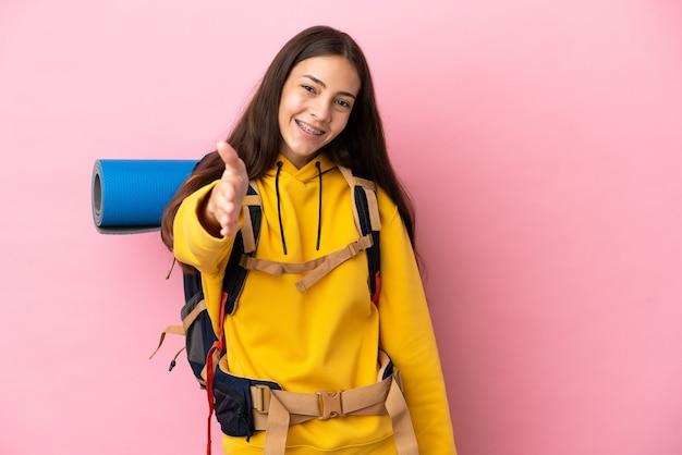 Junges bergsteigermädchen mit einem großen rucksack einzeln auf rosafarbenem hintergrund, der sich die hände schüttelt, um ein gutes geschäft abzuschließen