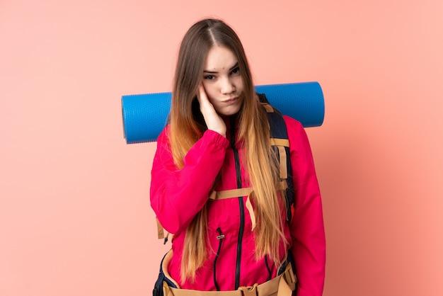 Junges bergsteigermädchen mit einem großen rucksack lokalisiert auf rosa wand unglücklich und frustriert