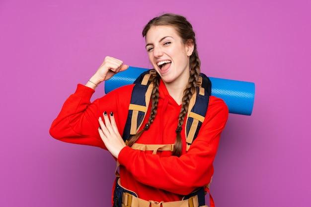 Junges bergsteigermädchen mit einem großen rucksack über der lokalisierten purpurroten wand, die starke geste macht