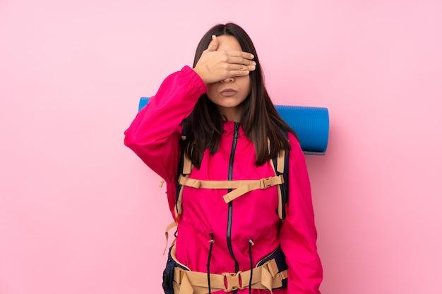 Junges bergsteigermädchen mit einem großen rucksack über isolierten rosa wand, die augen durch hände bedeckt. ich will nichts sehen