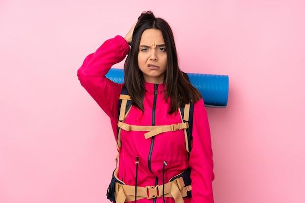Junges bergsteigermädchen mit einem großen rucksack über isolierter rosa wand mit einem ausdruck der frustration und des nichtverständnisses
