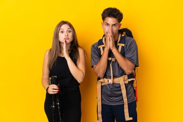 Junges bergsteigerpaar mit einem großen rucksack auf gelb hält handfläche zusammen. person fragt nach etwas