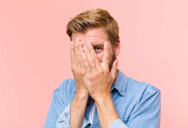 Junges blondes erwachsenes mannbedeckungsgesicht mit den händen, spähend zwischen finger mit überraschtem ausdruck und schauen zur seite