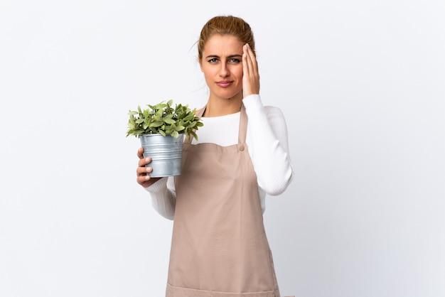 Junges blondes gärtnerfrauenmädchen, das eine pflanze über isolierter weißer wand hält, unglücklich und frustriert mit etwas. negativer gesichtsausdruck