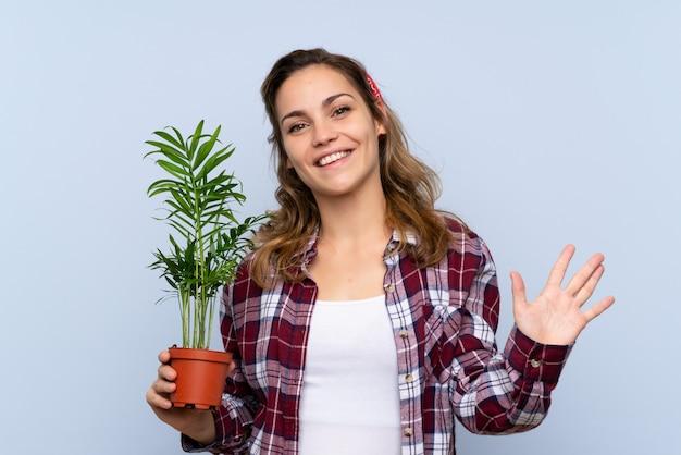 Junges blondes gärtnermädchen, das eine anlage begrüßt mit der hand mit glücklichem ausdruck hält