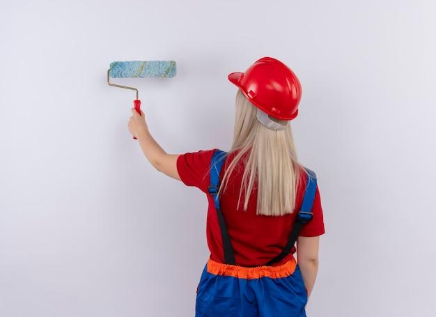 Junges blondes ingenieur-baumeistermädchen in der einheitlichen malwand mit farbroller, der in der ansicht hinten auf der isolierten weißen wand steht
