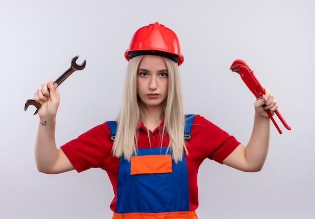 Junges blondes ingenieur-baumeistermädchen in der uniform, die den offenen endschlüssel und den rohrschlüssel hält, die auf isolierte weiße wand schauen