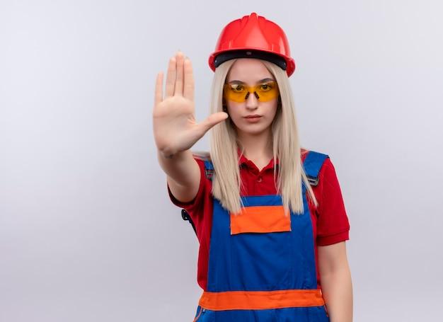 Junges blondes ingenieur-baumeistermädchen in der uniform, die die sicherheitsbrille trägt, die hand gestikulierenden halt auf isolierter weißer wand mit kopienraum ausdehnt