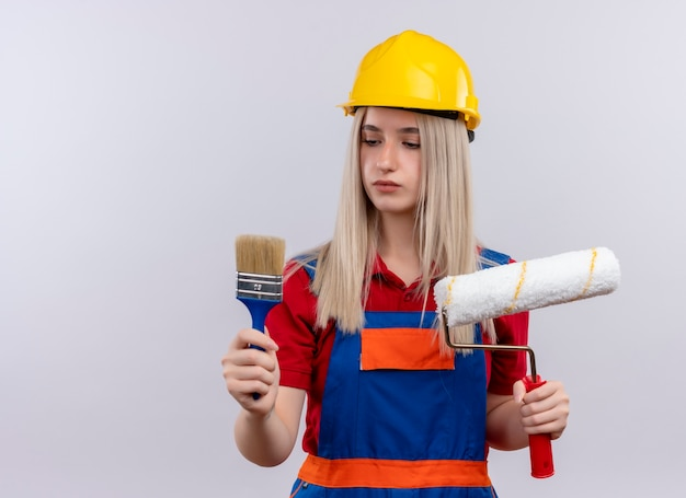 Junges blondes ingenieur-baumeistermädchen in der uniform, die pinsel und rolle hält und sie auf isolierter weißer wand mit kopienraum betrachtet