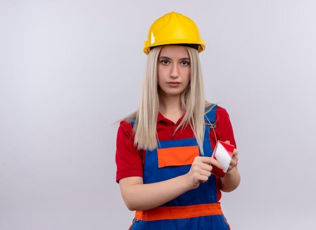 Junges blondes ingenieurbaumeistermädchen in der uniform, die klebeband hält, das auf isolierte weiße wand mit kopienraum schaut