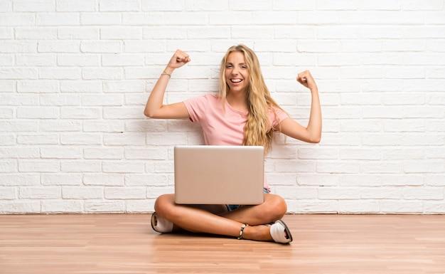 Junges blondes kursteilnehmermädchen mit einem laptop auf dem fußboden einen sieg feiernd