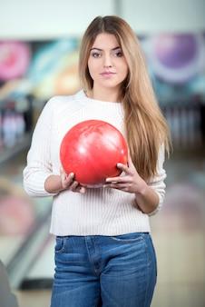 Junges blondes lächelndes mädchen, das bowlingspiel spielt.