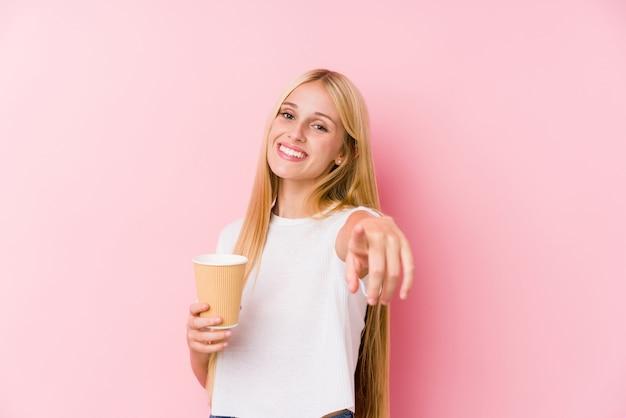 Junges blondes mädchen, das ein fröhliches lächeln des kaffee zum mitnehmen hält, zeigt nach vorne.