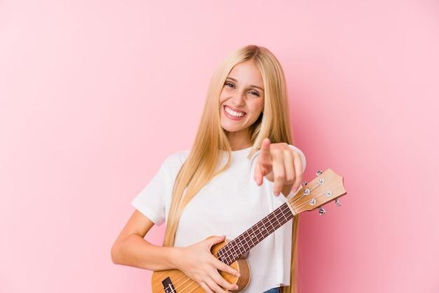Junges blondes mädchen, das fröhliches lächeln der ukelele spielt, zeigt nach vorne.