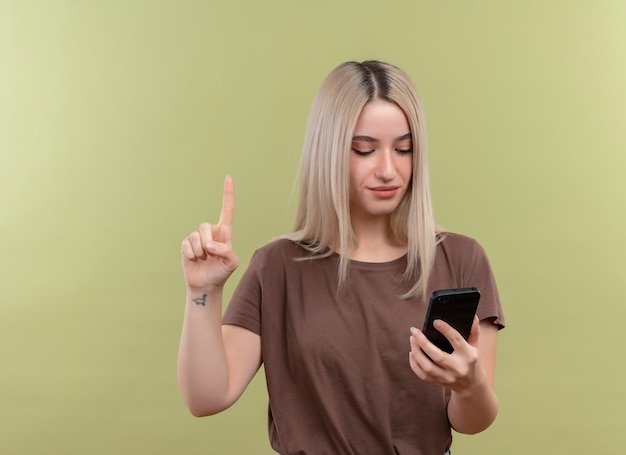 Junges blondes mädchen, das handy hält, das es mit erhöhtem finger auf isolierter grüner wand mit kopienraum betrachtet