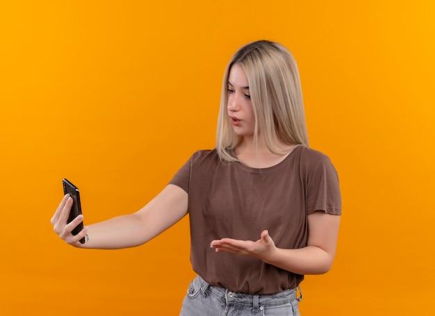 Junges blondes mädchen, das handy hält und mit der hand darauf auf lokalisierte orange wand zeigt