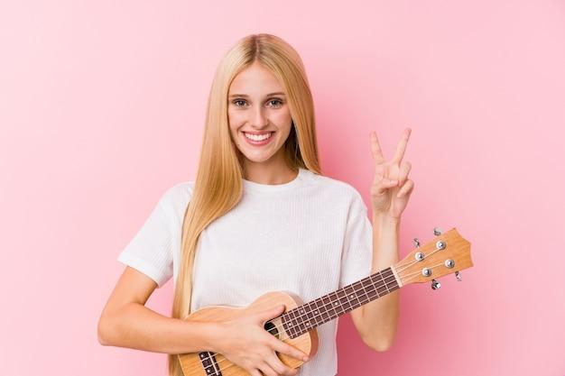 Junges blondes mädchen, das ukelele spielt, das siegeszeichen zeigt und breit lächelt.