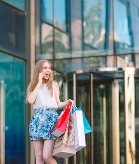 Junges blondes mädchen des lebensstilporträts, wenn die einkaufstaschen vom shop heraus gehen und mit dem handy sprechen.