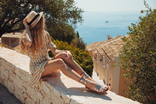 Junges blondes mädchen im sommerkleid, das türkisfarbenes meer betrachtet