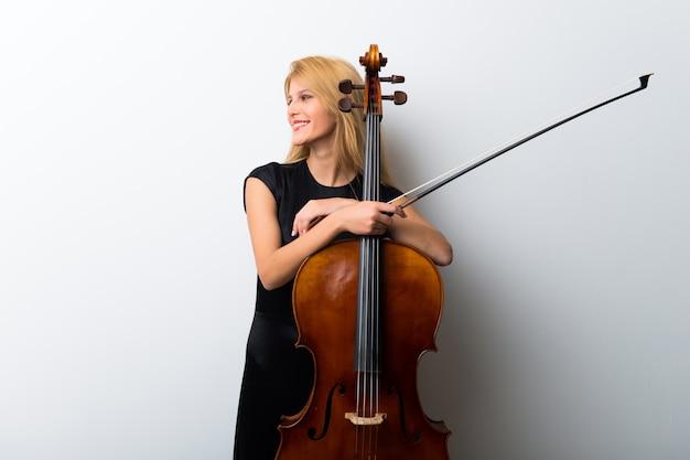 Junges blondes mädchen mit ihrem cello, das auf weißer wand aufwirft