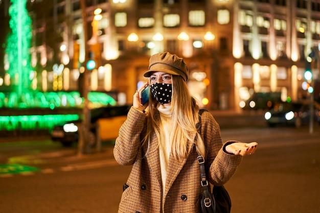 Junges blondes mädchen mit maske, die am telefon spricht und mit ihren händen gestikuliert. sie ist nachts in einer stadt. winteratmosphäre.