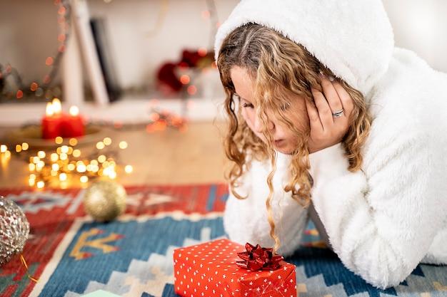 Junges blondes mädchen mit weihnachtsgeschenk in weihnachtsatmosphäre