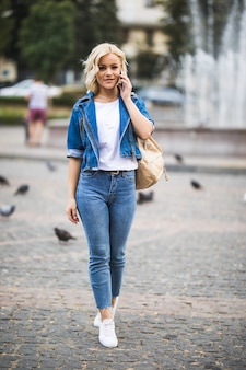 Junges blondes mädchen spricht am telefon auf straßenwegquadrat-fontain, gekleidet in blue jeans suite mit tasche auf ihrer schulter in sonnigem tag