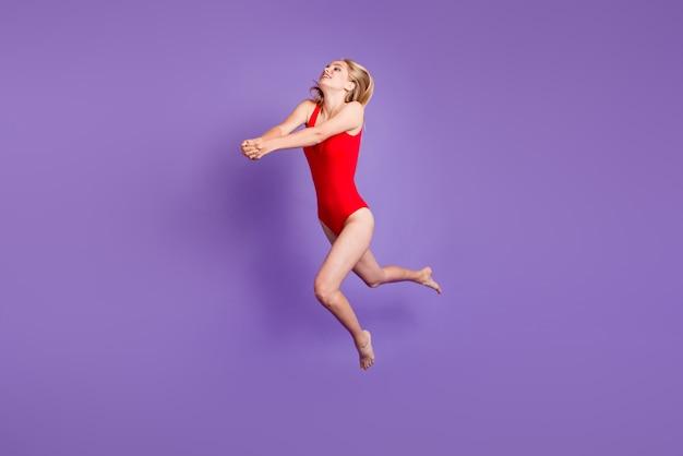Junges blondes mädchen springen hoch und tritt volleyball isoliert auf violett