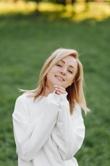 Junges blondes mädchen trägt einen weißen kapuzenpulli, der lächelt und im wald geht
