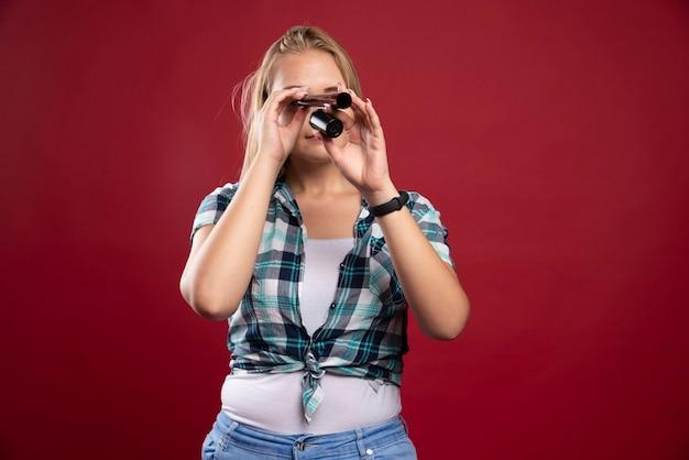 Junges blondes model, das durch eine polaroid-filmröhre schaut und spaß hat.