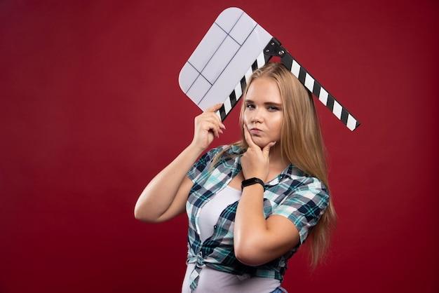 Junges blondes model, das einen leeren film hält, der eine klappe dreht, und sieht verwirrt aus.