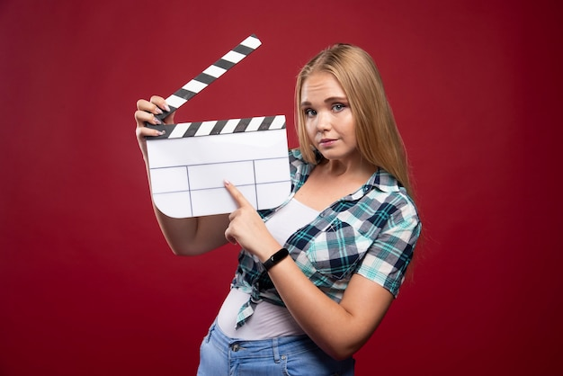 Junges blondes model, das einen leeren film hält, der eine klappe dreht und spaß hat. Kostenlose Fotos