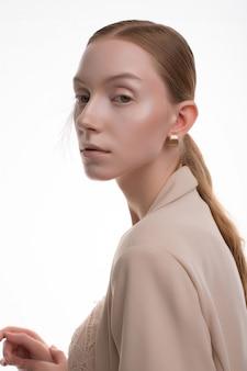Junges blondes modell mit kunstmake-up, das im beigen rockanzug aufwirft