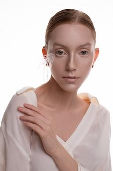 Junges blondes modell mit kunstmake-up im weißen outfit, das im weißen studio aufwirft