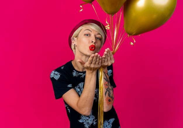Junges blondes partygirl, das partyhut hält, der ballons hält, die kamera sehen, die schlagkuss lokalisiert auf purpurrotem hintergrund mit kopienraum sendet