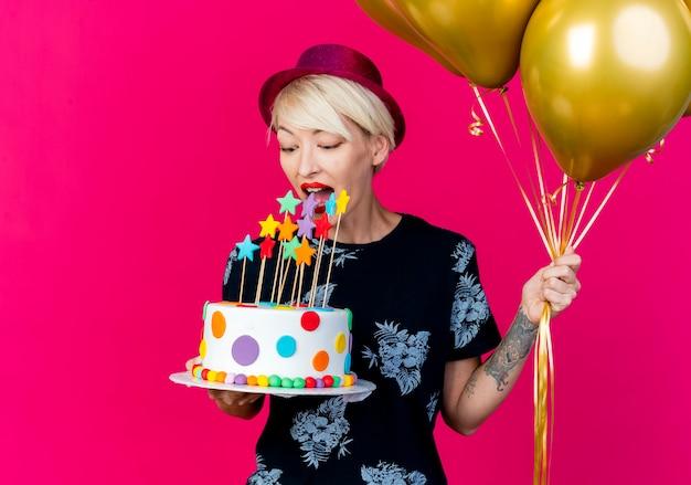 Junges blondes partygirl, das partyhut hält, der luftballons und geburtstagstorte mit sternen hält, die versuchen, kuchen lokalisiert auf purpurrotem hintergrund mit kopienraum zu beißen
