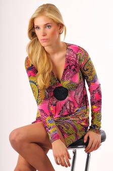 Junges blondes schönes frauenmodell im rosa kleid mit orientalischem muster, das auf barstuhl über heller wand im foto sitzt. beauty- und fashion-lifestyle-konzept