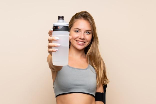 Junges blondes sportmädchen über lokalisierter wand mit sportwasserflasche