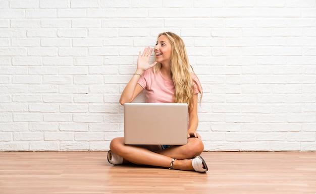 Junges blondes studentenmädchen mit einem laptop auf dem boden, der mit dem breiten mund schreit, öffnen sich