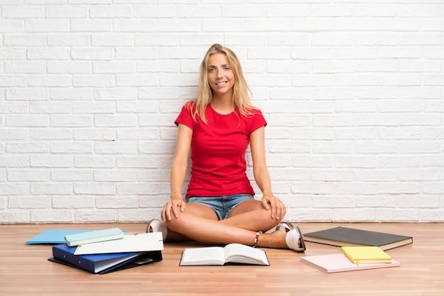 Junges blondes studentenmädchen mit vielen büchern auf dem boden, der zweifel hat und mit verwirren gesichtsausdruck