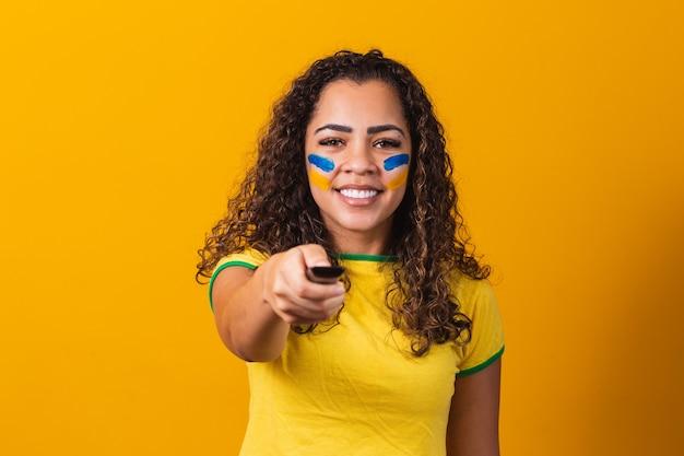 Junges brasilianisches fanmädchen mit controller in der hand, das bereit ist, das brasilianische spiel zu sehen