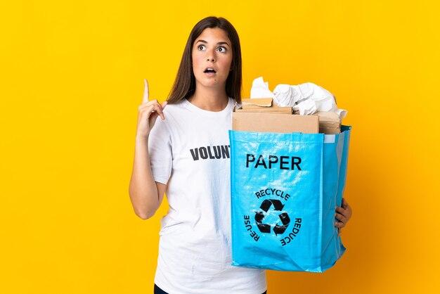 Junges brasilianisches mädchen, das einen recyclingbeutel voll papier hält, um lokalisiert auf gelber wand zu recyceln, die eine idee denkt, die den finger nach oben zeigt