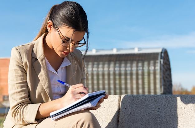Junges brünettes mädchen, das auf einer parkbank außerhalb ihres büros arbeitet. schreiben in ihre agenda. geschäftskonzept, technologie und telearbeit.