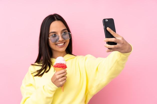 Junges brünettes mädchen, das ein kornett-eis über isoliertem rosa hintergrund hält und ein selfie macht