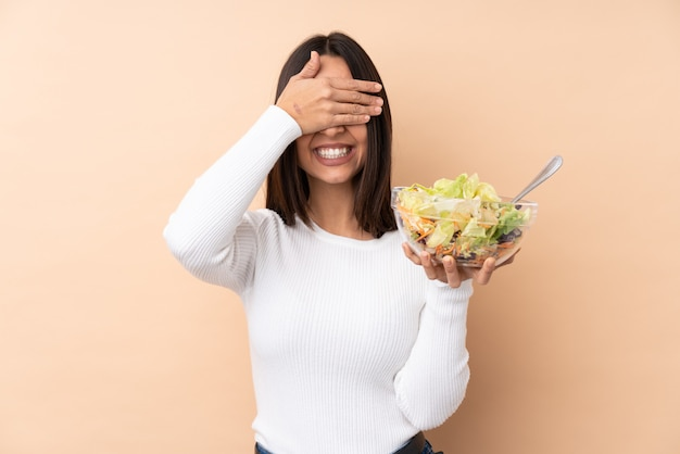 Junges brünettes mädchen, das einen salat über isolierten wandabdeckungsaugen durch hände hält. ich will nichts sehen