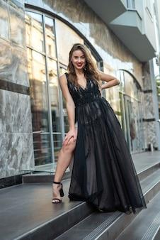 Junges brünettes mädchen im eleganten schwarzen abendkleid, das nahe an der vorderseite des glasgebäudes aufwirft