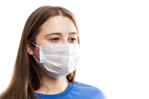 Junges brünettes mädchen in einer maske. coronavirus-pandemie und saisonale allergien. auf weißer wand isoliert. nahansicht.