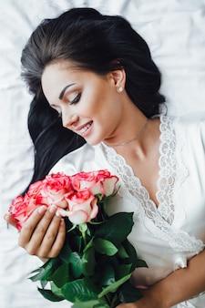 Junges brünettes mädchen liegt morgens auf ihrem bett und hält schöne rosen in den händen. ansicht von oben.