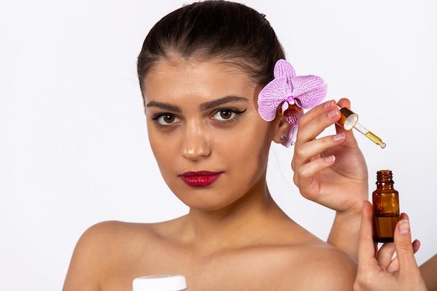 Junges brünettes mädchen mit sanftem make-up, das mit gesichtsserum aufwirft. kosmetologie, hautpflege, spa, naturkosmetik. foto auf weißer wand. hochwertiges foto